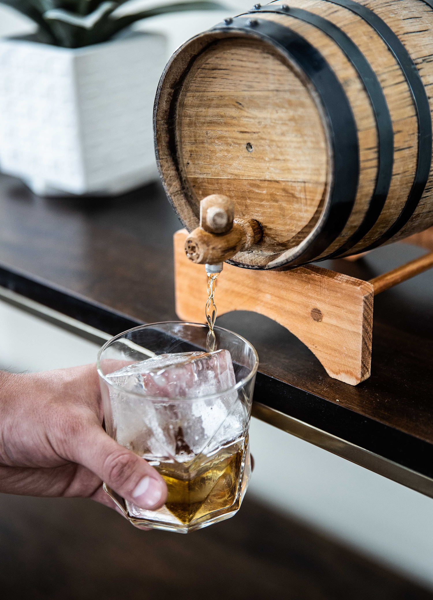 Pouring barrel-aged Greenpoint cocktail from two-liter barrel