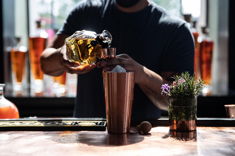 Elliott Clark pouring tequila for berry margaritas