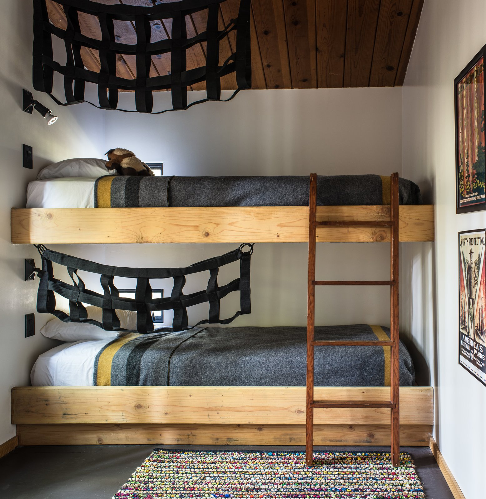 In the second bedroom, built-in bunk beds add an element of playfulness, decorated with black netting.