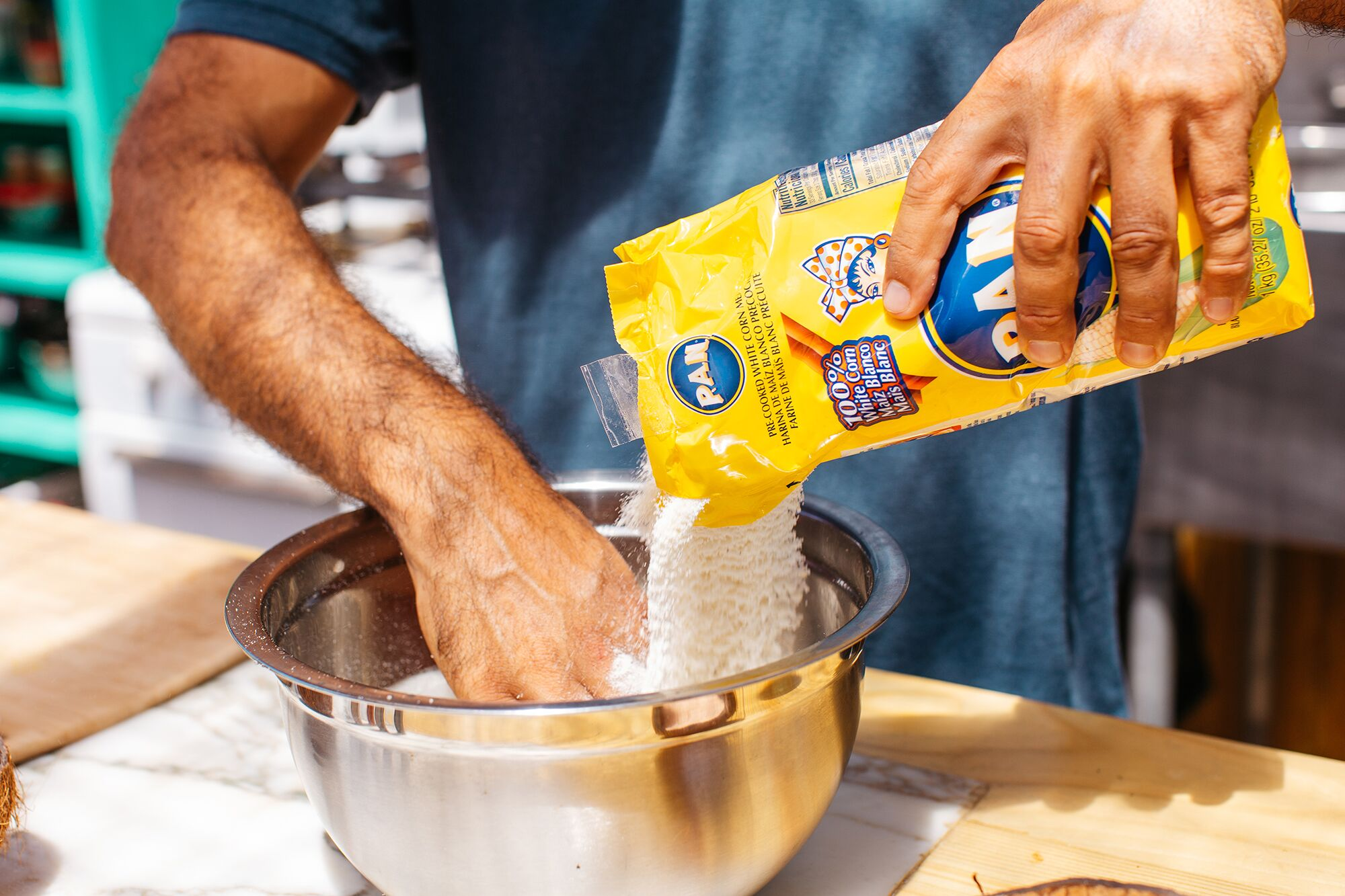 Chef Dario Tani pours cornmeal for arepas