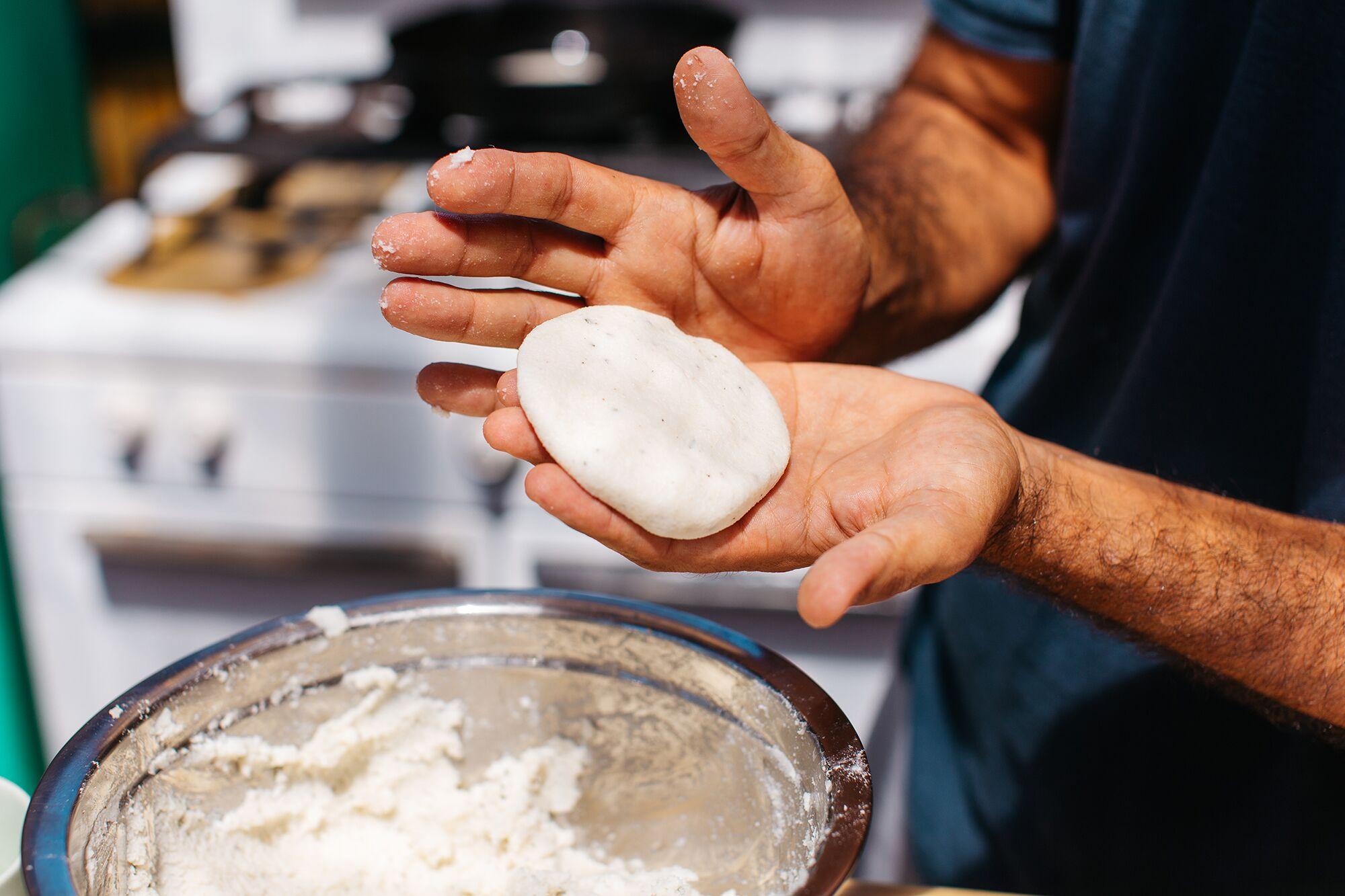 Chef Dario Tani shapes arepas